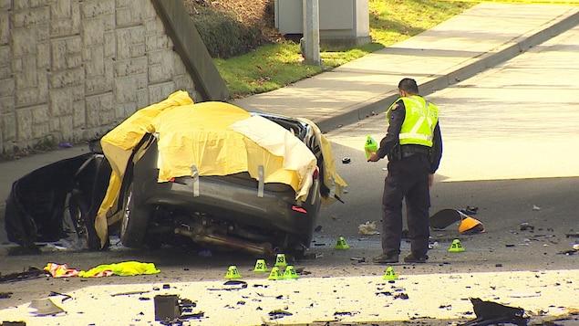 Une voiture écrasée recouverte d'une bâche en plastique jaune.