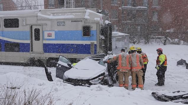 Une voiture emboutie par un train entourée de pompiers et secouristes.