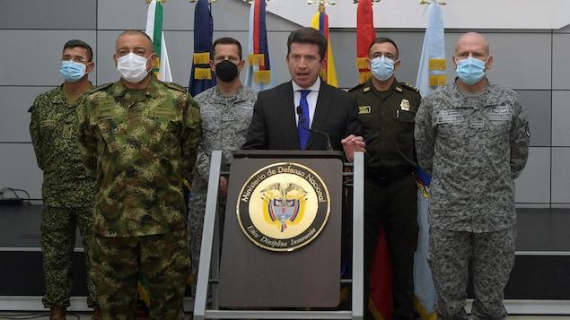 Un homme debout devant un pupitre entouré de soldats