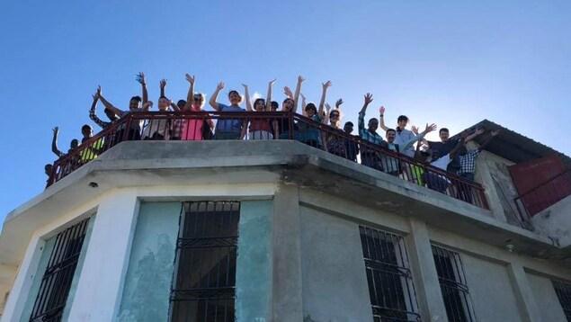 Une vingtaine de personnes situées sur le toit d'un édifice envoie la main au photographe.