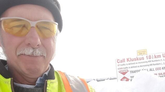 Photo d'un homme avec un chapeau, des lunettes et une moustache.