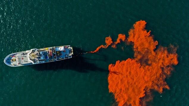 Du colorant orange qui est dispersé à partir d'un bateau.