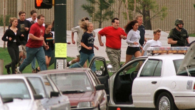 Des étudiants et des enseignants courent à l'extérieur de l'école.