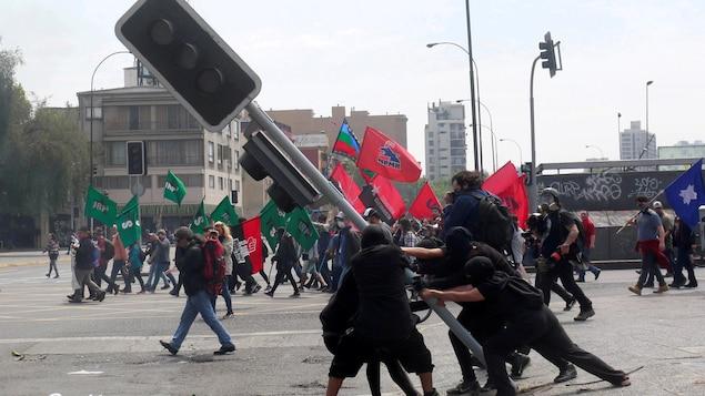 Des manifestants font tomber un feu de signalisation routière à Santiago, au Chili.