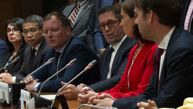 Des membres du Grand Comité international sur les mégadonnées, la protection des renseignements personnels et de l'éthique sont assis au cours d'une conférence de presse, pendant laquelle le député conservateur Bob Zimmer répond à la question d'un journaliste.
