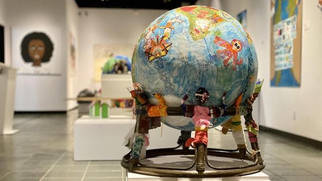 Une sculpture représentant la planète terre, soutenue par des sculptures de personnes provenant de différentes cultures.