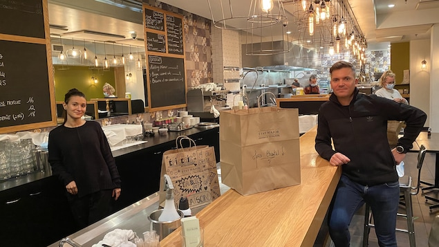 Une femme et un homme, séparés par un comptoir, dans un restaurant.