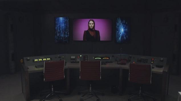 Un bunker futuriste où l'on aperçoit une femme androïde sur un écran face à une salle de commande.