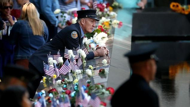 Un homme en uniforme regarde le site où était autrefois le World Trade Center, entouré de fleurs et de drapeaux américains.