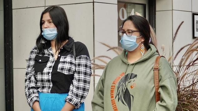 Deux personnes portant des bijoux et vêtements autochtones.