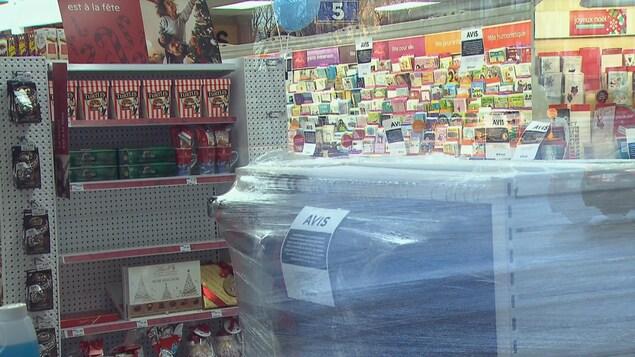 Une étagère d'une pharmacie recouverte de plastique pour s'assurer que les clients n'achètent pas le produit.