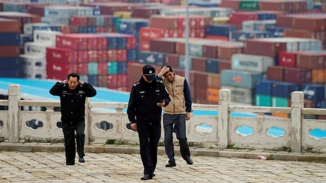 Des gardiens de sécurité marchent dans un port. En arrière-plan, des centaines de conteneurs.