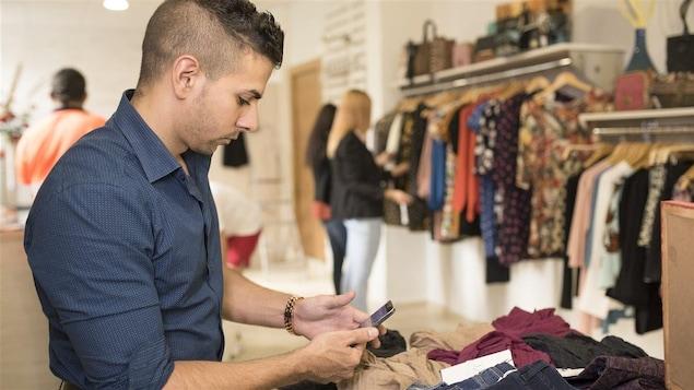 Un employé dans une boutique de vêtements placé devant des clientes qui magasinent