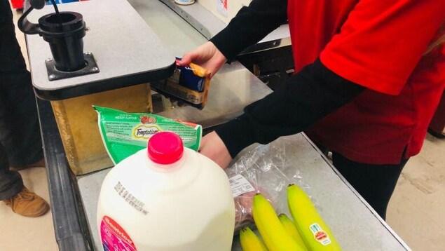 Une caissière scanne des aliments dans une épicerie.