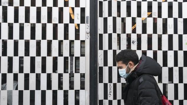 Un homme portant un masque passe devant un commerce qui est fermé.