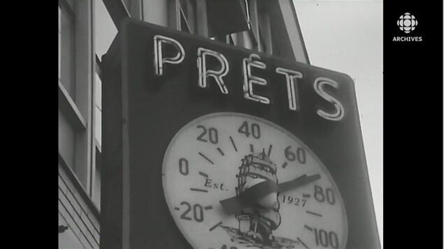 Enseigne d'une commerce de prêt avec une horloge pivotante.