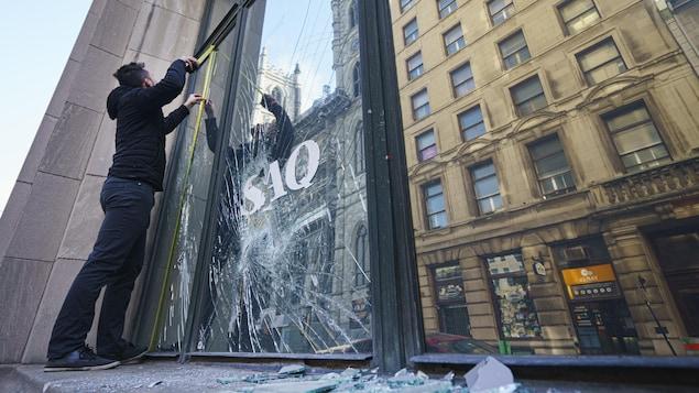 Un homme prend des mesures afin de remplacer une vitrine qui a été cassée dans une SAQ.