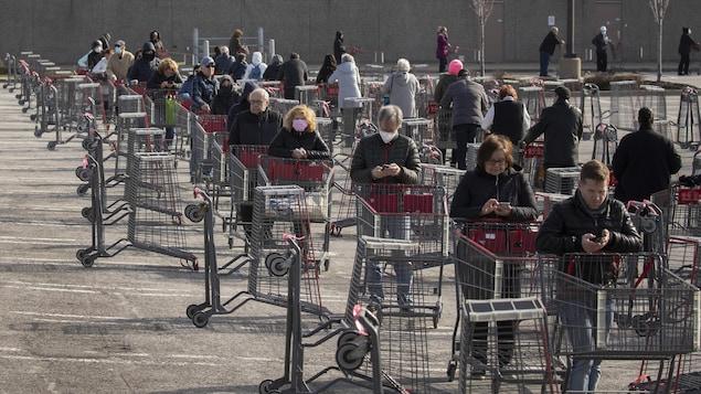 Des clients font la file avec des paniers dans le stationnement d'un commerce.