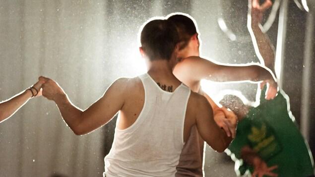 Des hommes dansent  de dos avec une lumière en arrière.