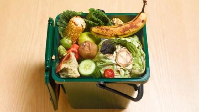 Un petit contenant de compost ouvert contient des restes de légumes et de fruits, dont de la laitue, du maïs et une banane.