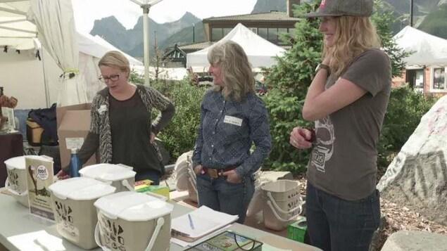 Trois femmes derrières une table sur laquelle se trouve de petits contenants à compostage.