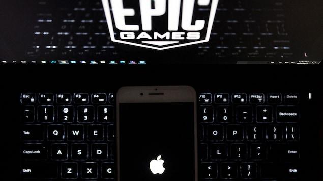 Le logo d'Apple affiché sur un téléphone, qui est déposé sur un clavier d'ordinateur dont l'écran affiche le logo d'Epic Games.