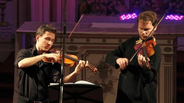Deux violonistes en concert.