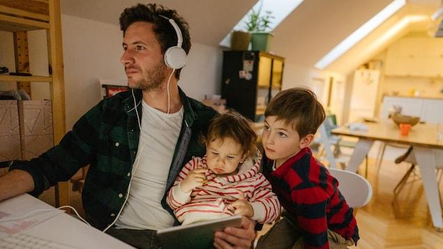 Un homme travaille en compagnie de sa fille et de son garçon à ses côtés.
