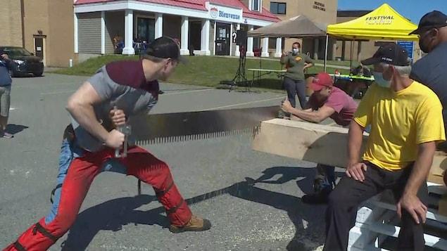 Deux hommes coupent un madrier avec une scie devant des  témoins.