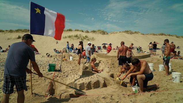 Un homme ratisse le tour de sa sculpture. Un drapeau acadien est planté dans le sable à côté.