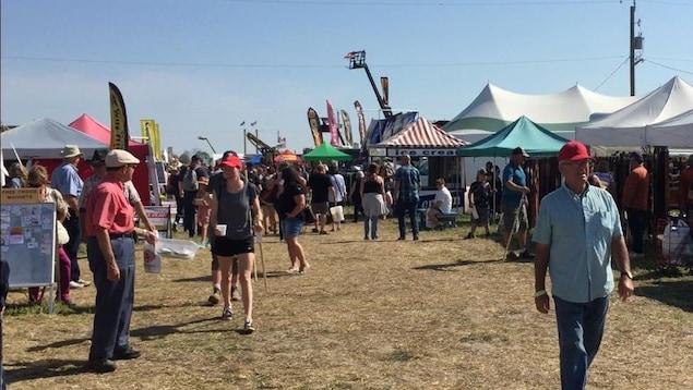 Des gens marchent sur un champs avec beaucoup de chapiteaux.