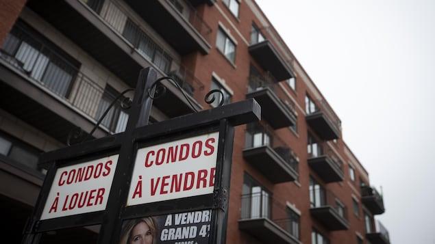 Cartel indicando condominios en venta y alquiler con un edificio al fondo.