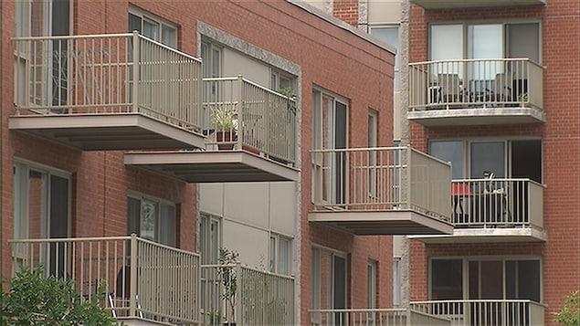 Vue sur des balcons d'un immeuble à condos avec des plantes et des chaises.