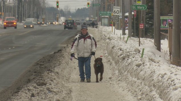Un homme marche sur un trottoir enneigé, le long d'une route.