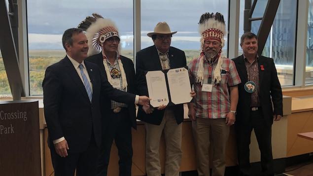 Les trois chefs de la Confédération, le ministre Ric Wilson et le premier ministre Jason Kenney posent avec le document du protocole d'entente.