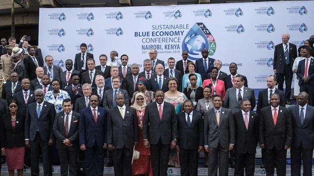 Des chef d'état et des ministres posent pour une photo de groupe devant une banderole de la conférence sur l'économie bleue durable.