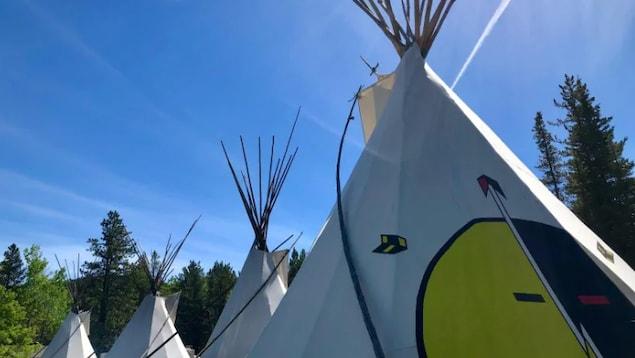 Des tentes autochtones sous un ciel bleu.