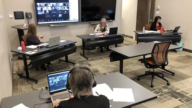Trois personnes dans une salle de conférence, chacune à son bureau, participe à un appel conférence vidéo.