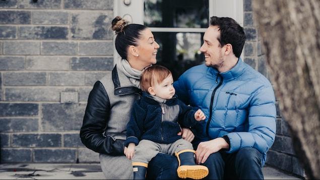 Une photo de famille.  Un père, une mère et leur jeune fils.