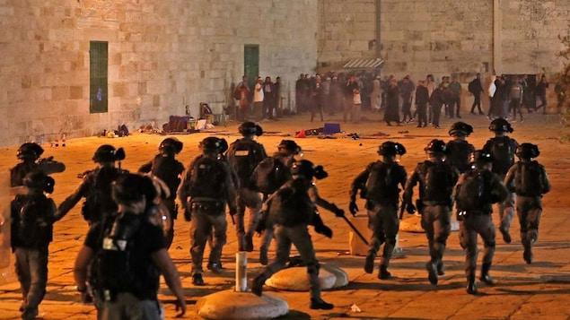 Des dizaines de policiers courent vers des dizaines de manifestants.