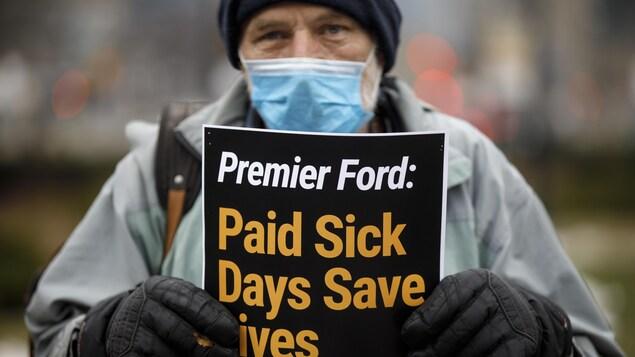 Un homme portant un masque chirurgical montre une affiche.