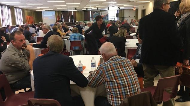 Des dizaines de délégués discutent en petits groupes dans une salle.