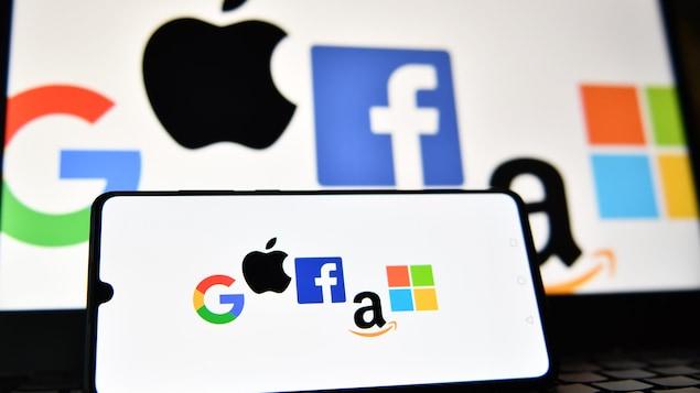 Les logos de Google, Apple, Facebook, Amazon et Windows affichés sur un téléphone intelligent et sur un écran d'ordinateur portable.