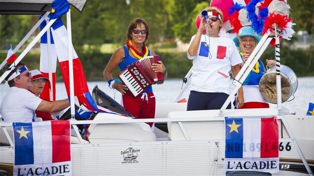 Sur un bateau, plusieurs personnes font la fête aux habillés aux couleurs de l'Acadie.