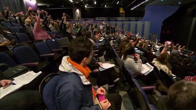 Les délégués sont assis dans un auditorium et votent.