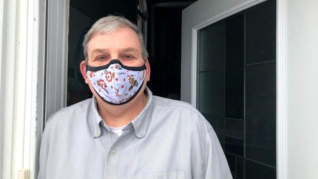 Conrad Tittley portant un masque dans un cadre de porte, regardant la caméra.
