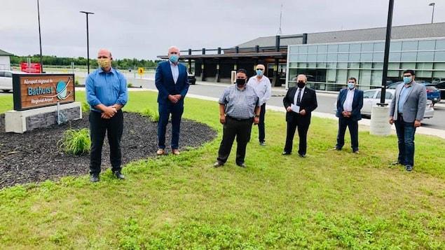 7 hommes portant un masque de protection se tienne debout à l'extérieur devant l'aéroport régional de Bathurst.