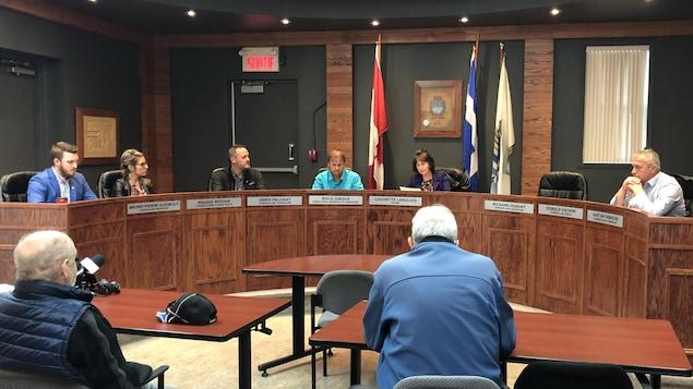 Des hommes et des femmes assis dans la salle du conseil de Chandler.