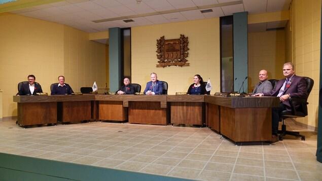 Tous les élus du conseil municipal de Matane assis à leur place à la table du conseil de Ville.