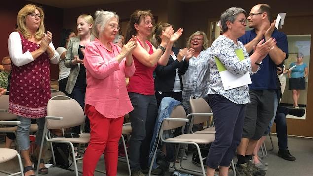 Des personnes se lèvent et applaudissent durant une séance du conseil municipal.